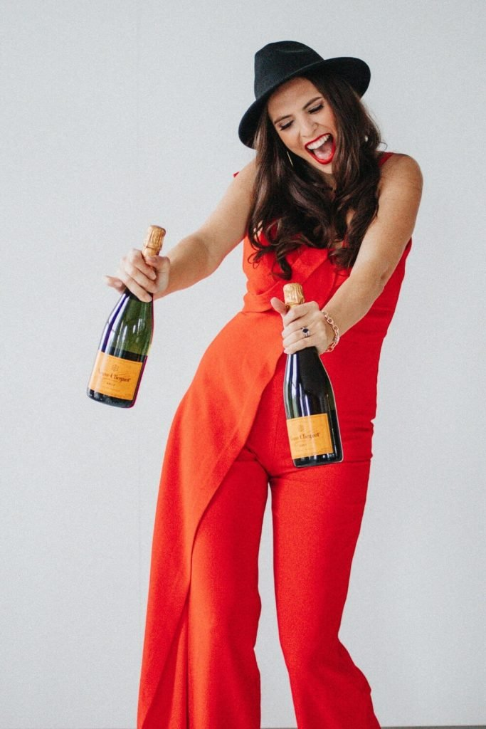 Cait smiling with 2 champagne bottles - business coaching for women
