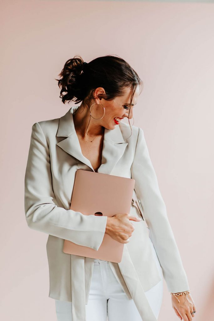 Cait with laptop and looking to side - female business coach